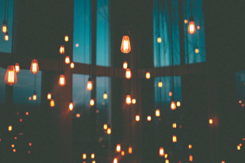 Symbolbild: Dunkler Raum mit alten Glühbirnen, die herunterhängen.